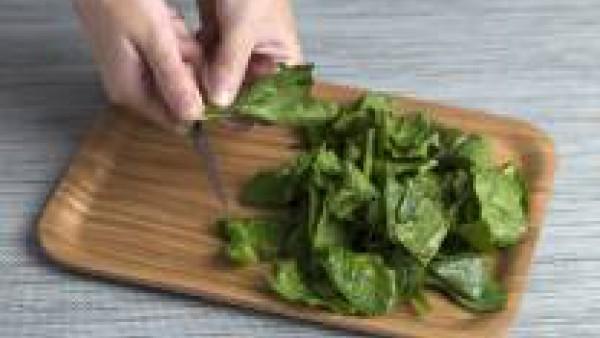 Lava las espinacas, escúrrelas y quítales el tallo. Pela el diente de ajo, lamínalo y dóralo en una olla con la mantequilla y un chorro de aceite de oliva.