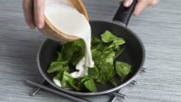 Saltea unas hojas de espinaca fresca con un chorrito de aceite de oliva. Sirve la crema en platos, añade las espinacas salteadas por encima y unas gotas de nata para decorar.