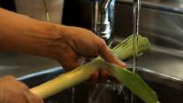 Lava el puerro: quítale las hojas externas. Elimínale las raíces y realízale un corte longitudinal en la parte superior. Pasa la hortaliza por agua. Con un dedo, separa las dos mitades del puerro, de