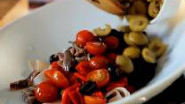 Mientras, pica el jamón, el pimiento y las anchoas en trozos pequeños. Lava los tomates cherry y pártelos por la mitad, y corta también las aceitunas por la mitad. Mezcla todos estos ingredientes en u