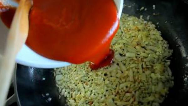 Mientras, en una sartén con un poco de aceite, sofríe la cebolla, picada. Cuando empiece a tomar color, añade el Tomate Frito Gallina Blanca y condimenta con el orégano, la pimienta y el pimentón. Dej