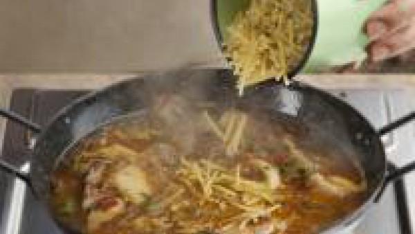 Cuando estén todos los ingredientes bien doraditos, añade el caldo, llévalo a ebullición y añade los fideos, los mejillones, las almejas y las gambas. Cuando los fideos estén listos, espolvorea el pim