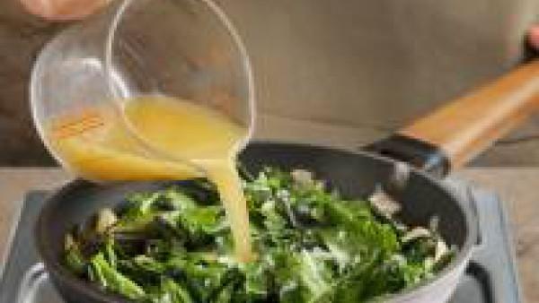 Añade 4 huevos batidos y remueve en la sartén hasta que empiecen a cuajar.