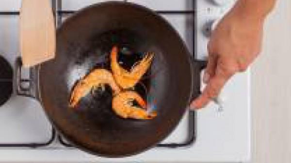 Saltea las gambas en el wok con un poco de aceite de oliva y 1 pastilla de Avecrem Dúo Paella de Pescado. Pica finamente el aguacate con la ayuda de un cuchillo afilado.