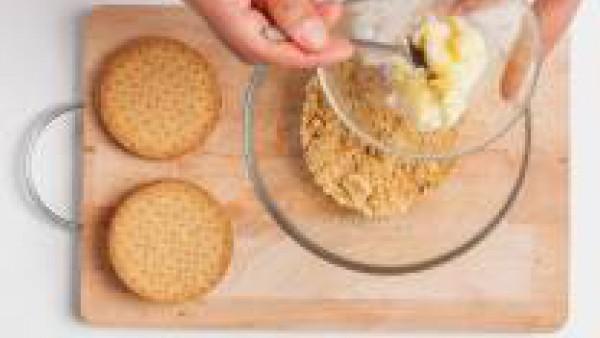 Añade la mantequilla a temperatura ambiente a las galletas aplastadas.   Mezcla y trabaja los ingredientes para crear una masa homogénea.