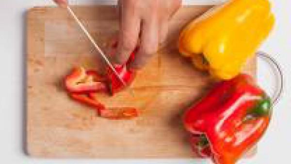 Lava los pimientos, quítales las semillas y córtarls.  Saltea los pimientos con el aceite de oliva virgen extra y un diente de ajo con piel.  Añade el Sofrito de Tomate y Verduras Gallina Blanca y coc