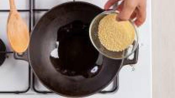 Tuesta el cuscús durante unos minutos en un wok untado con aceite de oliva virgen extra. Sazona con sal y pimienta.   Mientras tanto, hidrata las pasas en agua caliente.