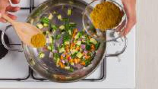 Agrega los vegetales salteados al curry y un poco de caldo que has reservado. Añade el arroz y mezclar bien.
