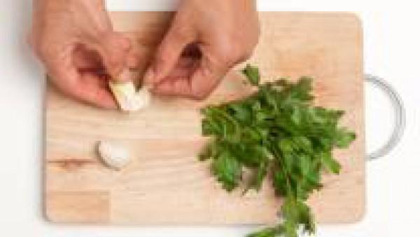 Pela los ajos y quita los tallos de perejil.  Pica el ajo y el perejil y mézclalos con aceite de oliva virgen extra.