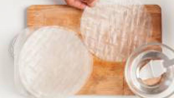 Prepara las hojas de arroz bañándolas con agua. Así conseguirás que sean mas suaves y fáciles de trabajar.  Llenar cada hoja con verduras y una cucharada de Tomate Frito Gallina Blanca. Después ciérra