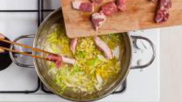 Agrega entonces la corteza, las salchichas y las costillas. Y, pasados 10 minutos, las bayas de enebro, y el repollo junto a 1 pastilla de Avecrem -30% Sal Carne. Cuece durante 20 minutos, añadiendo m