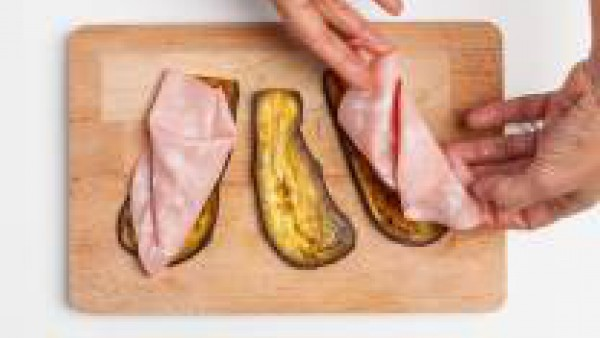 Retira las berenjenas del horno y coloca sobre cada una de ella una lámina de mortadela. Rellena también con los tomates y envuélvelo formando una especie de rollito.