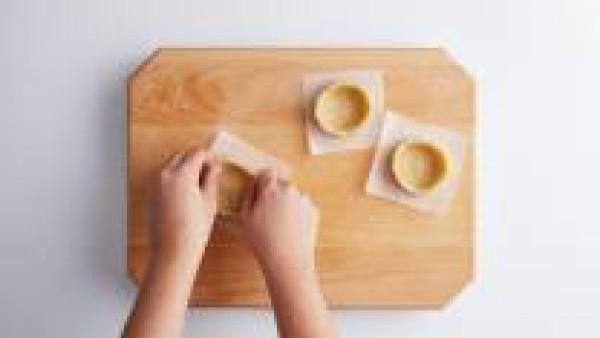 Con un cuchillo, corta en trocitos el cordero asado y resérvalo. Haz bolas de unos 80gr de masa y ponlas sobre trozos de papel de horno de unos 10x10cm. Con los dedos, forma tartaletas de unos 7-8cm d