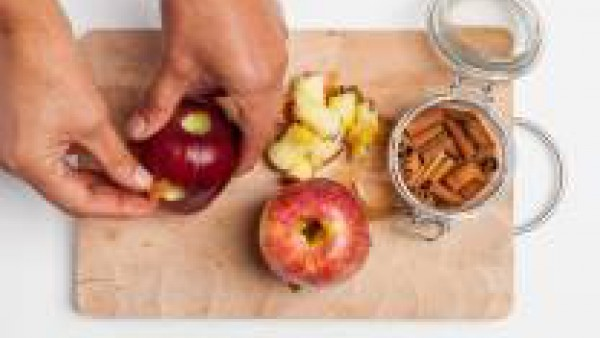Rellena las cavidades practicadas a cada manzana con 1 rama de canela y 1 trozo de chocolate negro. Dispón las manzanas en una bandeja forrada con papel de horno, espolvorea con azúcar y hornea a 200