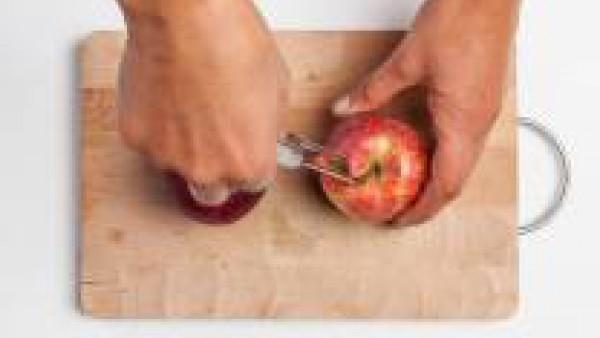 Lava las manzanas, retira su corazón y practica agujeros en la superficie de la fruta. Trocea una porción del chocolate negro (aproximadamente 100 g).