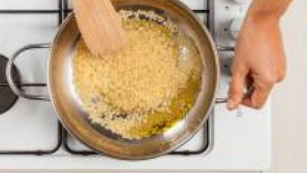 En otra sartén, fríe el arroz con 1 cucharada de aceite de oliva virgen extra