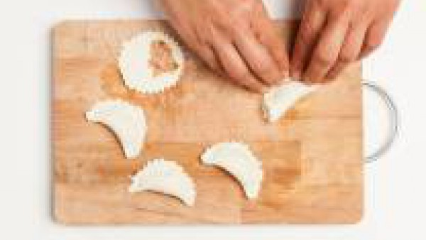 Después de haber cepillado de los bordes de los discos de masa con la leche, rellena los círculos de hojaldre con el atún y el tomate frito. Finalmente, dobla los discos formando medias lunas, presion