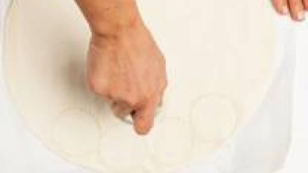 Extiende la masa de hojaldre y corta discos de masa utilizando un molde redondo. Precalienta el horno a 200°C.