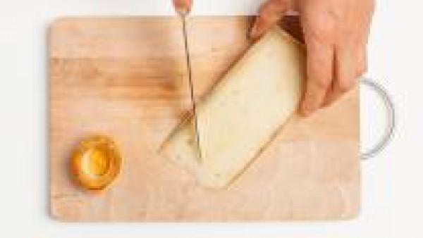 Corta el queso Emental o Gruyère en trozos de tamaño mediano. Mientras tanto, deja que el horno se caliente a 200°C.