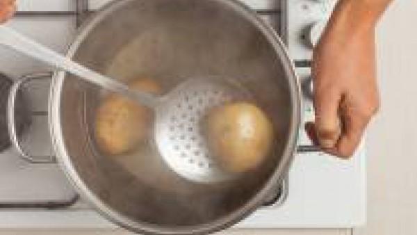 Lava y cocina las patatas en abundante agua con sal. Una vez cocidas, deja enfriar y luego pélalas.