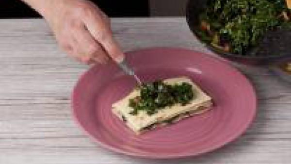 Monta la lasaña, para ello coloca en el fondo de cada plato una placa de lasaña, echa por encima 1 lámina de jamón y otra de queso. Añade por encima un poco de la mezcla de espinacas y tomate y repite