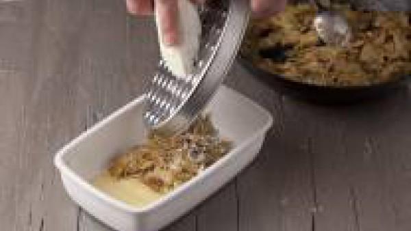 Ralla el queso rulo de cabra con la ayuda de un rallador grueso. Mi Salsa Bechamel Gallina Blanca, según las instrucciones del sobre. Monta la lasaña, en una fuente de horno honda, echa un poquito de