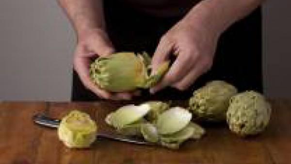 Corta el diente de ajo finamente. Corta la cayena por la mitad. En una cazuela echa un chorrito de aceite de oliva y cocina el ajo suavemente junto a la cayena. Prepara las alcachofas, para ello, pela