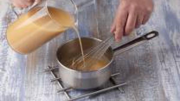 Prepara la crema de marisco, para ello echa en un cazo la mantequilla y deja que se funda, añade la harina de golpe y déjala cocinar un minuto. Echa el Caldo para Fideuá Fácil 100% Natural Gallina Bla