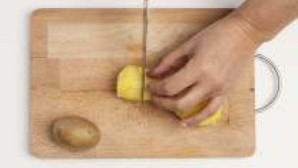 Mientras tanto, hierve las patatas en agua 1 pastilla de Avecrem Caldo de Pollo. Cuando estén cocidas, colócalas en una tabla de cortar, pélalas y córtalas por la mitad. Vacía un poco el interior de l