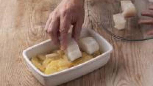 Añade el bacalao cortado encima de las patatas y cuece unos 7 minutos más en el horno, hasta que el bacalao y las patatas estén cocinados.