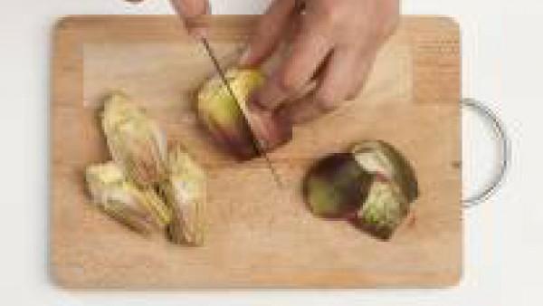 Limpia las alcachofas quitándoles las hojas exteriores, córtalas en trozos y déjalas en remojo en agua y limón para que no ennegrezcan.