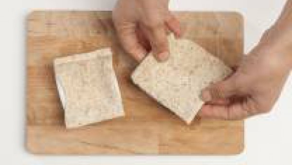 Con un rodillo, aplastar finas rebanadas de pan integral de sándwich