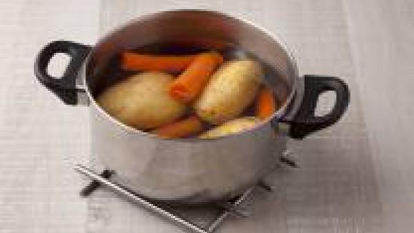 Cuece las patatas enteras en una olla con agua abundante durante 25-30 minutos. A mitad de cocción añade las zanahorias peladas. Deja cocinar hasta que las verduras estén tiernas, luego escúrrelas y e