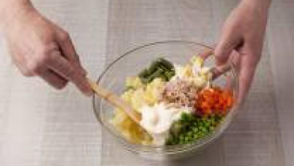 Mezcla en un cuenco las patatas, las zanahorias, los guisantes, las judías, los huevos, la mayonesa y el atún, y mézclalo con cuidado. Sírvelo con unas aceitunas por encima y unas tiras de pimientos d