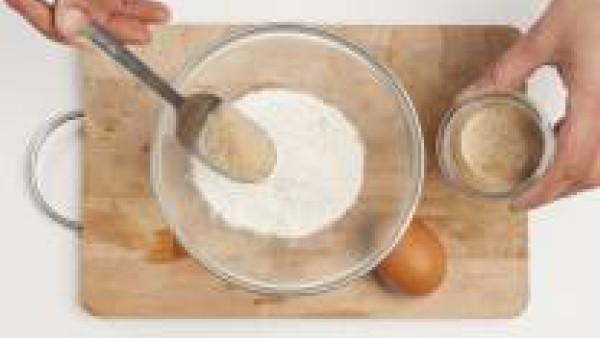 En un bol, mezcla la mantequilla ablandada con el azúcar moreno y los huevos, la harina, el polvo para hornear y la piel de naranja. Mézclalo hasta que la masa esté suave y homogénea.