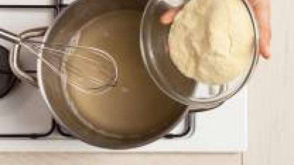 En una olla grande, pon a hervir el caldo de verduras, añade el azúcar moreno y la sémola, revolviendo constantemente con un batidor para evitar que se formen grumos. Aromatiza con el vino y continúa