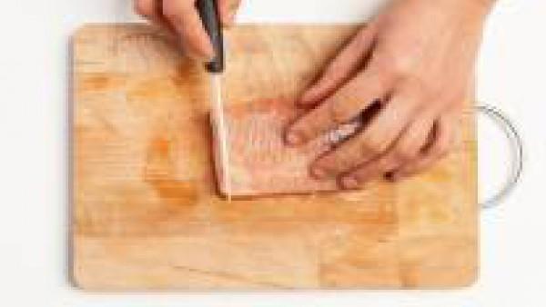 Mientras tanto, corta en rodajas finas el salmón y limpia las gambas, quítales el caparazón, el intestino y la cola.
