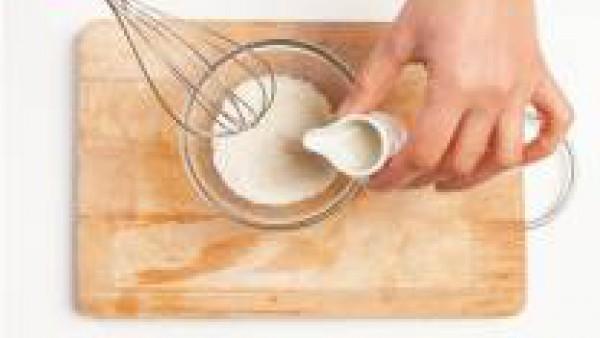 En un tazón, vierte 100 g de coco rallado y añade el azúcar, y las leches de arroz y coco. Añadir el agar agar, mueve todo en una cacerola y lleva a ebullición a fuego lento, revolviendo constantement