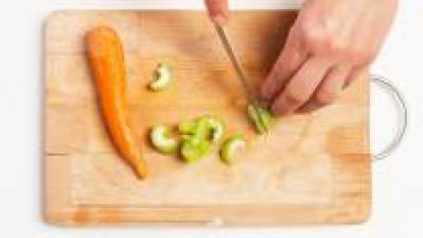 Pela y pica la cebolla; lava, limpia y corta las zanahorias y el apio en rodajas. En una sartén, rehoga la cebolla en 1 cucharada de aceite de oliva virgen extra; añade la zanahoria, el apio y el toma