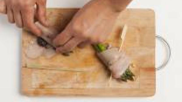Después de la cocción, dispón los filetes de pechuga de pollo en una tabla de cortar y rellénalos con el paté de aceitunas y los espárragos. Enróllalos y ciérralos con un pincho.