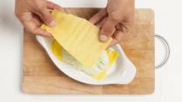 Corta la lasaña en la forma del recipiente de horneado, y unta el mismo con 1 cucharada de aceite de oliva, y cúbrelo con la pasta, alternando con capas de pesto y salsa bechamel. Comienza con una cap