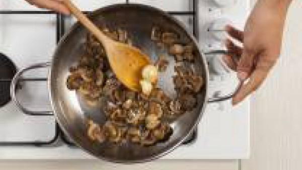 Limpia los champiñones y córtalos en rodajas finas. En una sartén, fríelos con los 2 dientes de ajo y 1 cucharada de aceite de oliva. Precalienta el horno a 200°C.