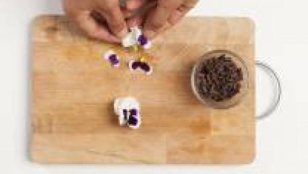Cuando la panacota esté lista sírvela en los platos con la ayuda del papel en la que está envuelta. Decora con el chocolate y los pétalos.