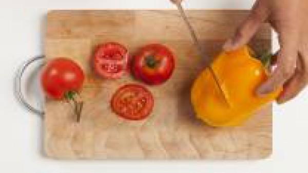 Lava las verduras; corta a rodajas longitudinales los calabacines, los tomates en rodajas y el pimiento en cuadrados. Por otra parte, en un bol, diluye el pesto con 1 cucharada de aceite de oliva.