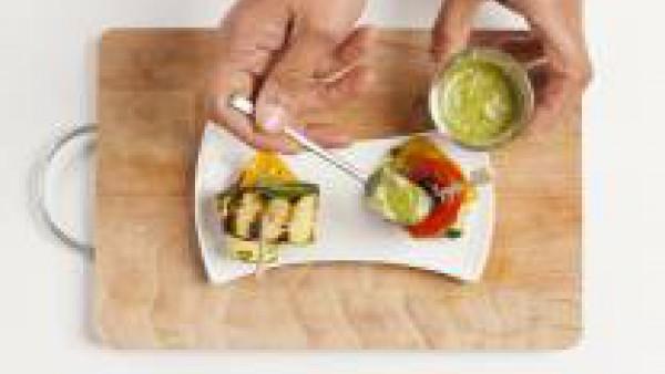 En un plato, forma torres con las verduras a la parrilla, alternando por el color. Utiliza un palillo para fijar el pincho. Adorna con 1 cucharada de pesto y sirve como aperitivo.