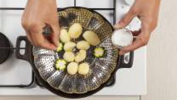 En una olla grande, coloca una malla metálica de vapor y organiza las verduras. Desmenuza 1/4 de pastilla Avecrem Verduras -30% de sal para que quede más sabroso y cocina tapado durante 10 minutos.