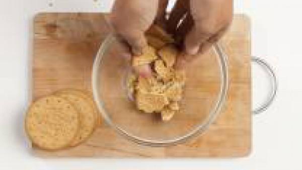 Mientras tanto, en un tazón, desmenuza las galletas integrales.