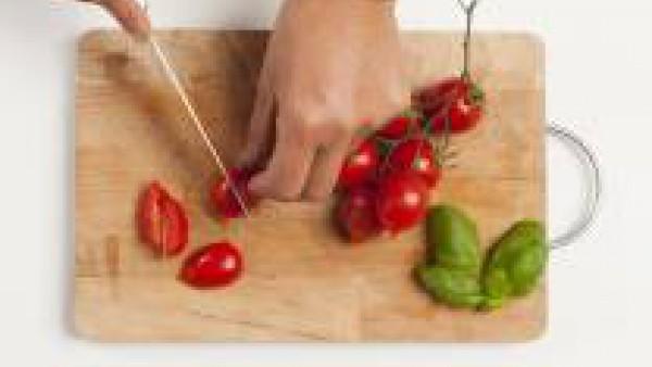 Lava los tomates y córtalos en trozos. Enjuaga y pica la albahaca.