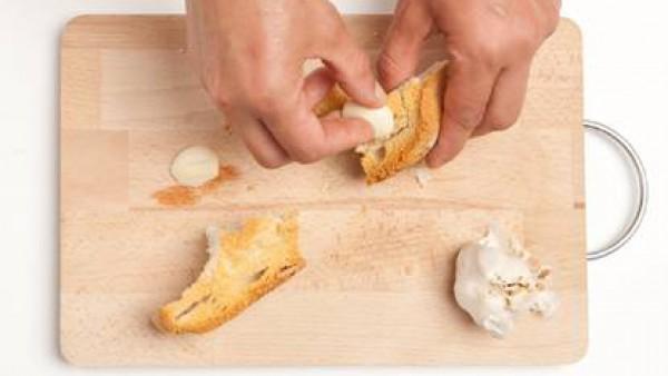 Rompe el pan en trozos bastante grandes y frota con ajo.