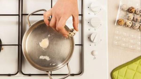 Prepara los huevos de codorniz escalfados. Calienta el agua en una cacerola con el vinagre blanco, cuando empieza a hervir reduce el fuego, casca el huevo y viértelo con una cuchara. Trata de cubrir e